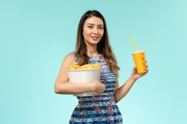 Cestino della holding della giovane femmina di vista frontale con patatine fritte e bevanda sulla superficie blu