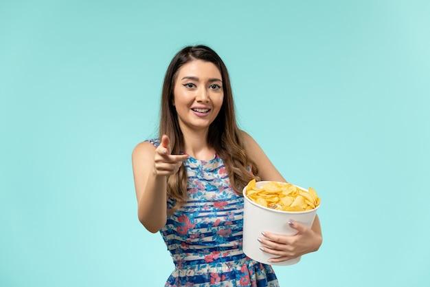 Cestino femminile giovane della tenuta di vista frontale con i chip che ride sulla superficie blu