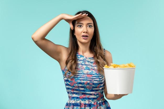 Cestino della holding della giovane femmina di vista frontale con i chip sullo scrittorio azzurro