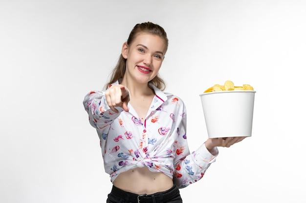 칩 바구니를 들고 흰색 표면에 웃는 전면보기 젊은 여성