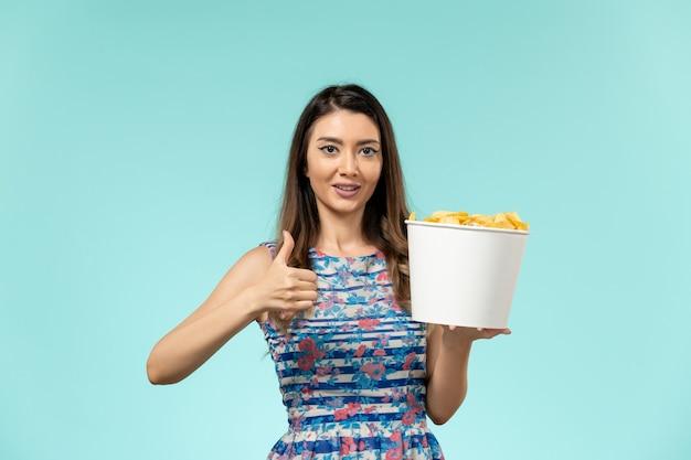 Cestino della holding della giovane femmina di vista frontale con i chip e guardare film sulla superficie blu