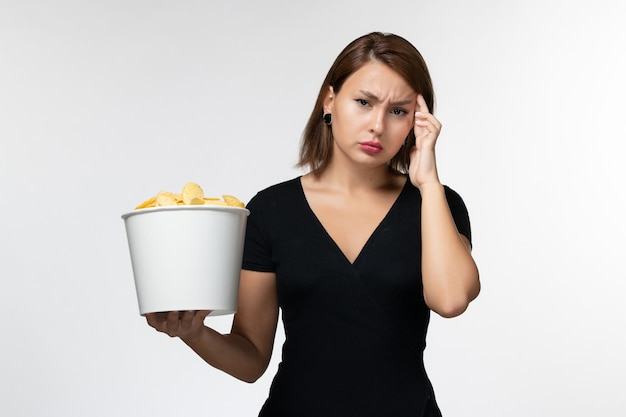 감자 칩 바구니를 들고 흰색 표면에 깊이 생각하는 전면보기 젊은 여성