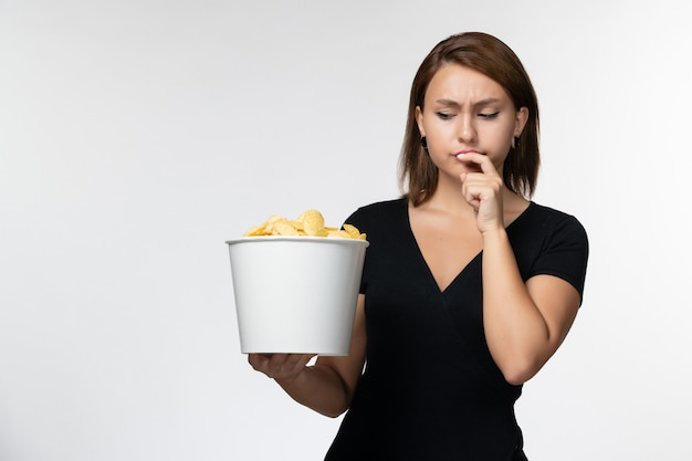 감자 칩 바구니를 들고 밝은 흰색 표면에 먹는 전면보기 젊은 여성