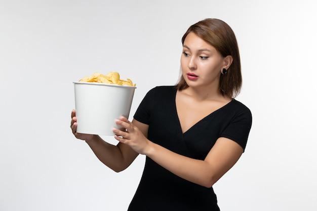 감자 칩 바구니를 들고 밝은 흰색 표면에 포즈 전면보기 젊은 여성