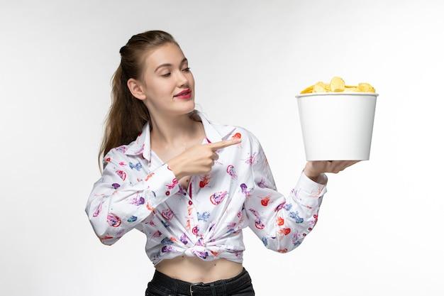 흰색 표면에 미소 감자 칩과 함께 바구니를 들고 전면보기 젊은 여성