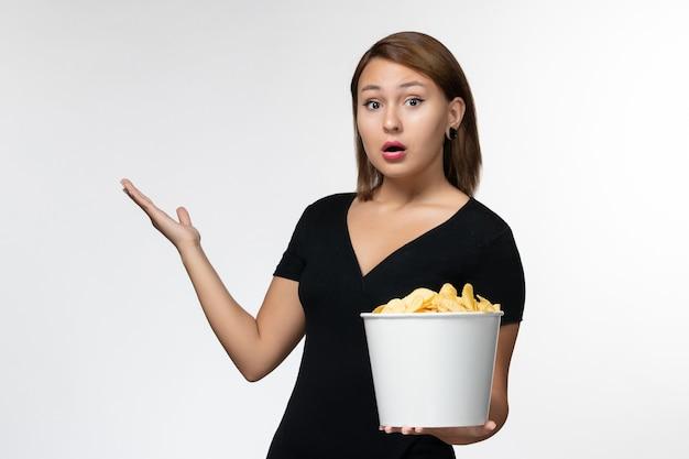 흰색 표면에 영화를보고 감자 칩과 함께 바구니를 들고 전면보기 젊은 여성