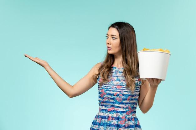 Cestino femminile giovane della tenuta di vista frontale con le patatine fritte sulla superficie blu