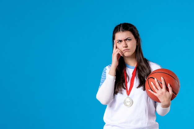 Front view young female holding basketball on blue wall