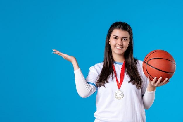 Вид спереди молодая женщина, держащая баскетбол на синей стене