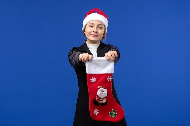 파란색 벽 새 해 이브 휴일에 큰 크리스마스 양말을 들고 전면보기 젊은 여성