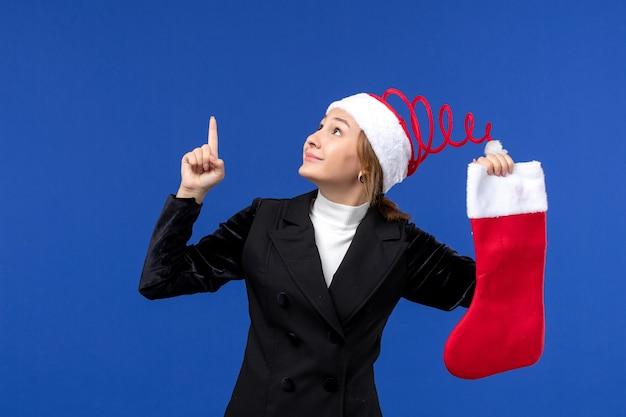 파란색 벽 인간의 새해 휴일에 큰 빨간 양말을 들고 전면보기 젊은 여성