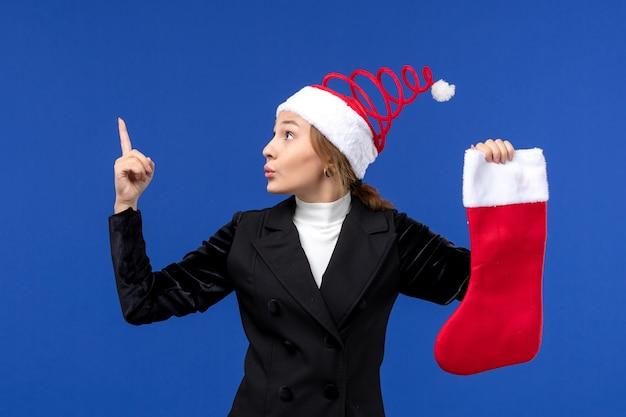 파란색 벽 인간의 새 해 휴일에 큰 빨간 양말을 들고 전면보기 젊은 여성