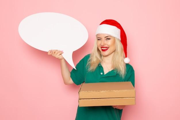 분홍색 벽 사진 작업 유니폼 새해 휴가 택배에 큰 흰색 기호와 음식 상자를 들고 전면보기 젊은 여성