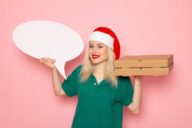 분홍색 벽 사진 작업 유니폼 새해 휴가 작업 택배에 큰 흰색 기호와 음식 상자를 들고 전면보기 젊은 여성