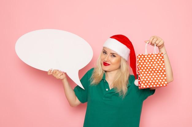 Вид спереди молодая женщина держит большой белый знак и присутствует на розовой стене фото цвета снега новогодний праздник женщина