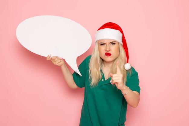 Vista frontale la giovane femmina che tiene grande segno bianco minaccia con rabbia sul muro rosa foto donna neve colore vacanze di capodanno