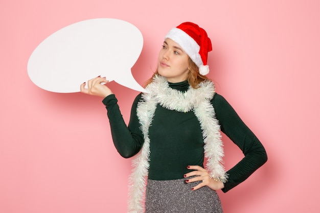 Front view young female holding big white sign on pink wall christmas new year model holiday color emotion