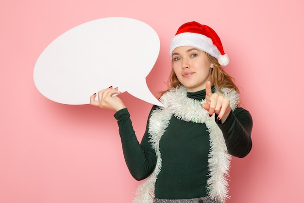 Front view young female holding big white sign on pink wall new year model holiday color emotion