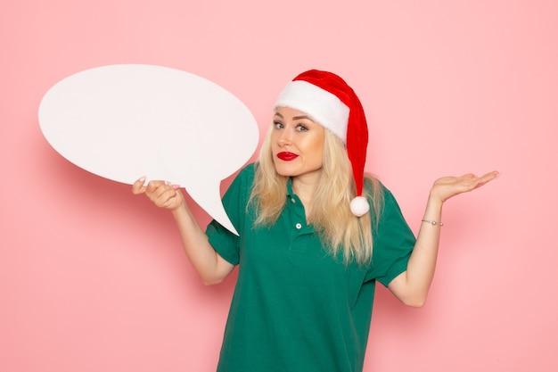 Vista frontale giovane femmina che tiene grande segno bianco sulla parete rosa foto neve colore capodanno vacanza donna
