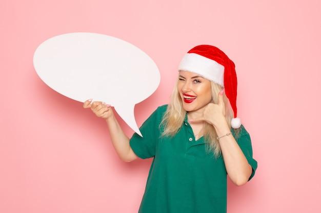 Vista frontale giovane femmina che tiene grande segno bianco sul muro rosa donna regali neve foto a colori vacanze di capodanno