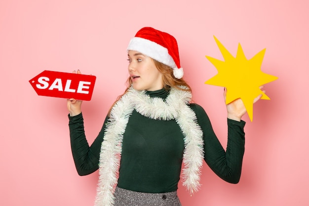 Вид спереди молодая женщина держит большую желтую фигуру и распродажу на розовой стене цветная модель праздники рождество, новый год эмоции