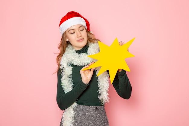 ピンクの壁の色の感情モデルの休日クリスマス新年に大きな黄色の図を保持している正面図若い女性
