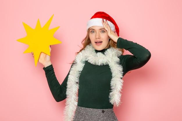 ピンクの壁モデルの休日のクリスマス新年の感情に大きな黄色の図を保持している正面図若い女性