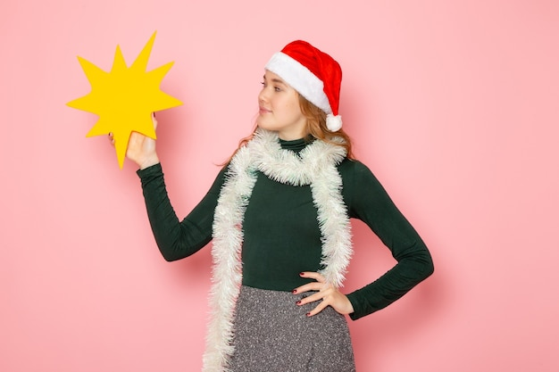 Front view young female holding big yellow figure on pink wall color emotions model holiday christmas new year