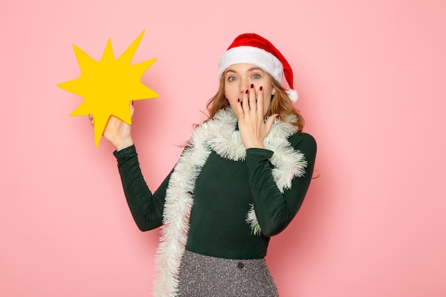 Front view young female holding big yellow figure on pink wall color model holiday new year emotion