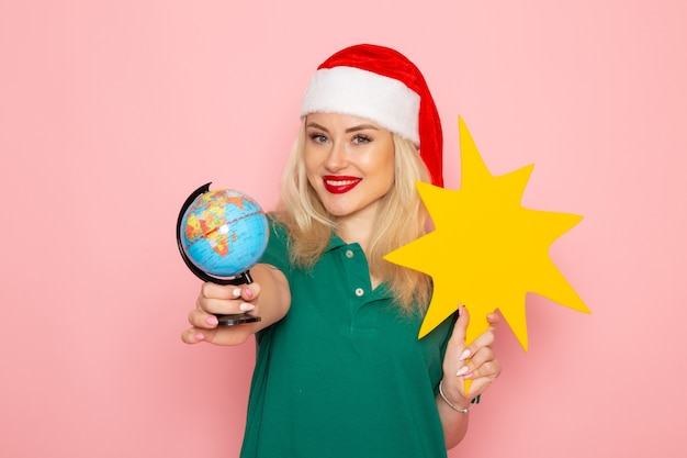 Front view young female holding big yellow figure on pink wall model woman xmas holiday photo new year color