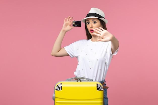 Vista frontale giovane donna con carta di credito nera su viaggio estivo a parete rosa chiaro