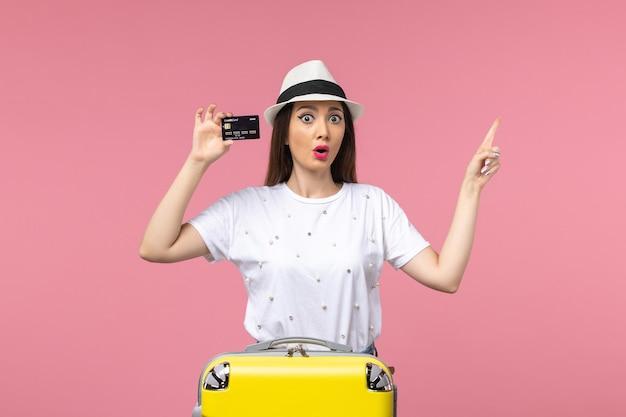 ピンクの壁の旅の航海の夏に黒い銀行カードを保持している正面図若い女性