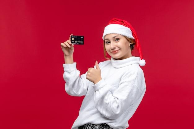 빨간색 배경에 검은 은행 카드를 들고 전면보기 젊은 여성
