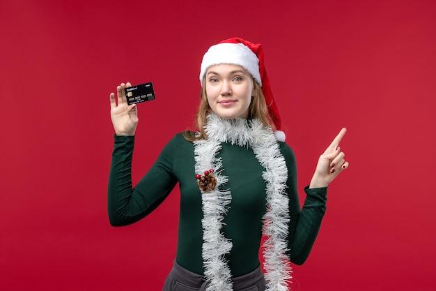 Вид спереди молодая женщина, держащая черную банковскую карту на красном столе