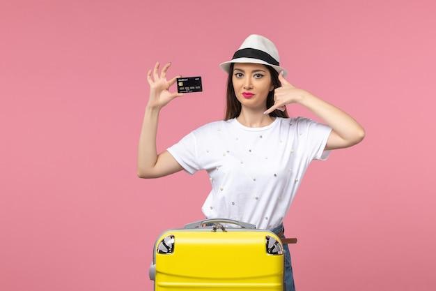 Vista frontale giovane donna in possesso di carta di credito nera sul viaggio estivo di viaggio a parete rosa