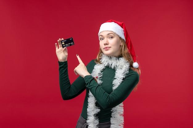 Giovane femmina di vista frontale che tiene carta di credito nera su fondo rosso