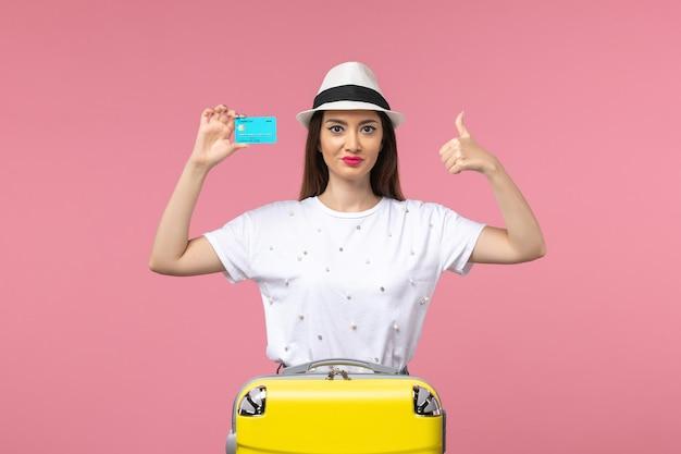 ピンクの壁の旅の航海の女性のお金で青い銀行カードを保持している正面図若い女性