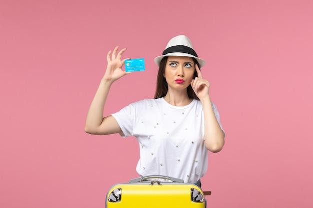 ピンクの壁の航海旅行の夏に青い銀行カードを保持している正面図若い女性