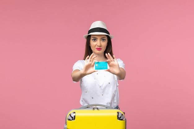 ピンクの壁の女性の旅行のお金の航海で青い銀行カードを保持している正面図若い女性