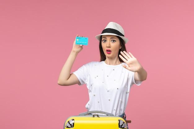 ピンクの壁の女性の旅行の航海のお金に青い銀行カードを保持している正面図若い女性