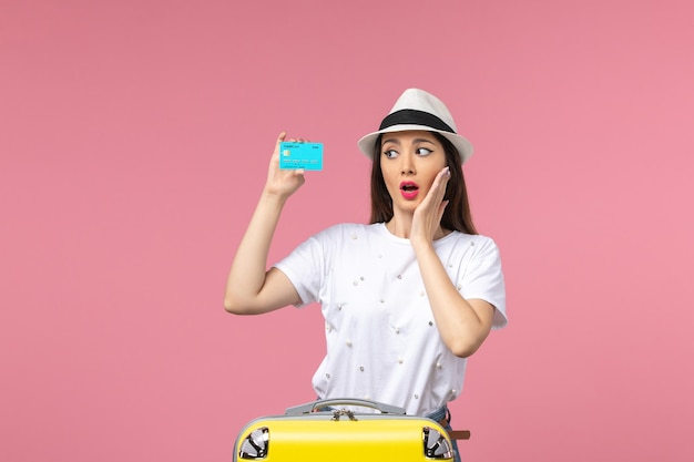 Вид спереди молодая женщина, держащая синюю банковскую карту на розовой стене, женщина, путешествие, путешествие, деньги
