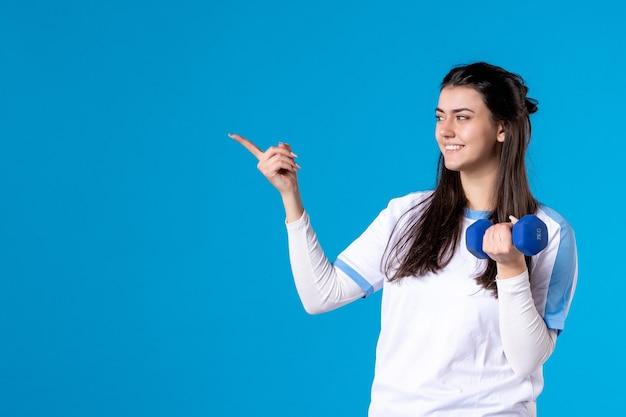Вид спереди молодая женщина держит синюю гантель на синей стене