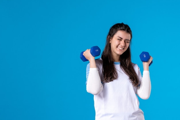 Front view young female holding blue dumbbells on blue wall Free Photo