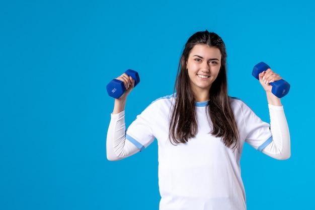 青い壁に青いダンベルを保持している正面図若い女性