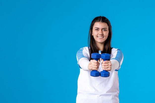 Вид спереди молодая женщина держит синие гантели на синей стене