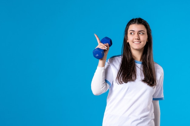 青いダンベルを保持している正面図若い女性