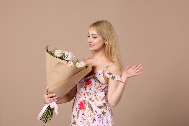Vista frontale di una giovane donna che tiene in mano un mazzo di bellissime rose sul muro marrone