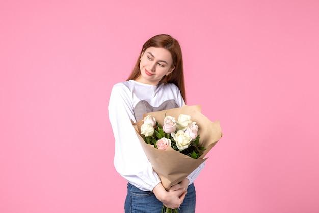 Vista frontale giovane donna che tiene un mazzo di belle rose sul rosa