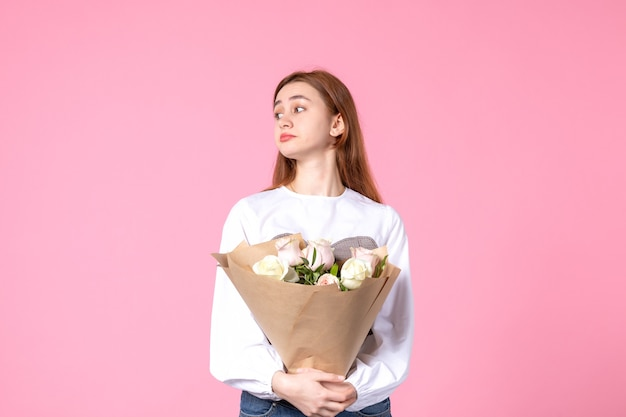ピンクの美しいバラの花束を保持している正面図若い女性