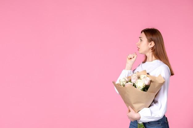 분홍색에 아름 다운 장미 꽃다발을 들고 전면 보기 젊은 여성